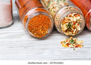 Jars with spices lying on a wooden countertop. Spices and dried vegetables pouring out of the jar. Lyophilized vegetables.