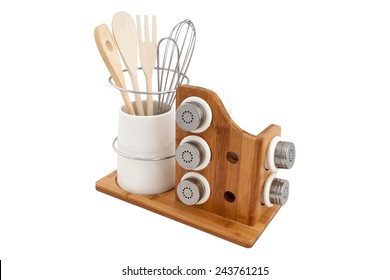 jars of spices and wooden cutlery on a wooden stand isolated on white background
