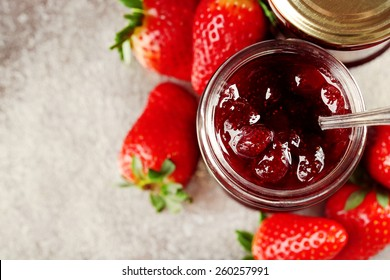 Jars of strawberry jam with berries on tray close up