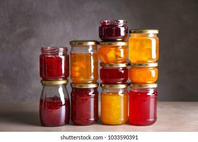 Jars with sweet jams on grey background