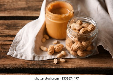 Jars with tasty peanut butter and nuts on wooden table