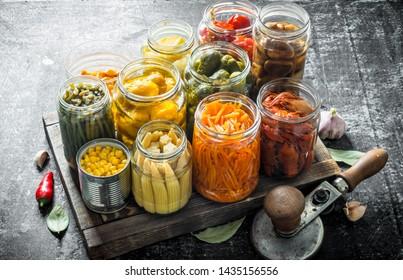Jars of various preserved food on tray. On dark rustic background