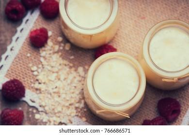 Jars with yogurt, raspberries and oat flakes