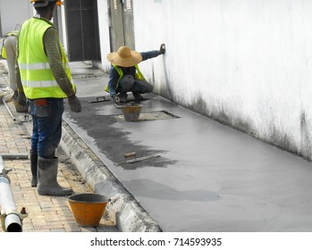 JASIN, MALAYSIA -SEPTEMBER 05, 2016: Construction workers leveling wet cement as the floor finishes on top of cement screed surface.