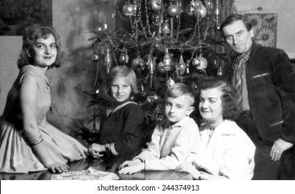JASLO,POLAND - DECEBMER 1958:vintage traditional photo of family around a Christmas tree