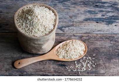 Jasmine brown rice in sack and in wooden spoon on a rustic wooden table.