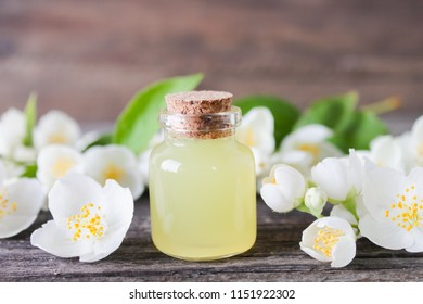 Jasmine essential oil and flowers on wooden table background.