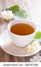 Jasmine green tea in a cup with jasmine flowers