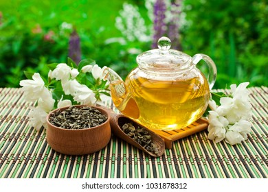 Jasmine green tea in a glass teapot with a wooden bowl, wooden scoop and fresh blossoms on a wooden table in the garden