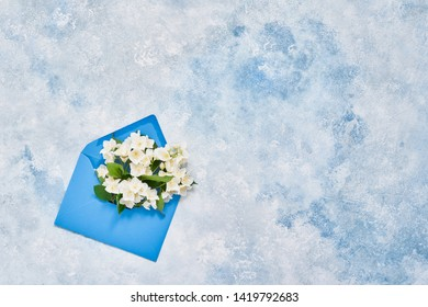 Jasmine, Philadelphus or mock-orange flowers in blue envelope on blue pastel background. Flat lay of Birhday, Mothers Day, bachelorette, Wedding concept. Copy space, top view.