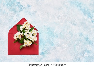 Jasmine, Philadelphus or mock-orange flowers in red envelope on blue background. Flat lay of Birhday, Mothers Day, bachelorette, Wedding concept. Copy space, top view.