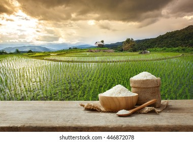 Jasmine Rice in bowl and burlap sack on wooden table with the rice field background with copy space