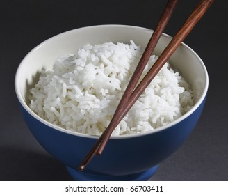 Jasmine rice in a rice bowl and wooden chopsticks isolated
