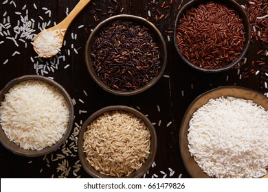 Jasmine rice, Brown rice, Red rice,Black rice, Mixed rice and Riceberry on rustic table, top view