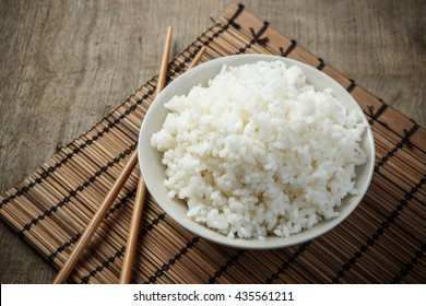 Jasmine rice with chopsticks on a bamboo placemat
