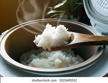 Jasmine rice cooking in electric rice cooker with steam. Soft Focus, Rustic tone picture.