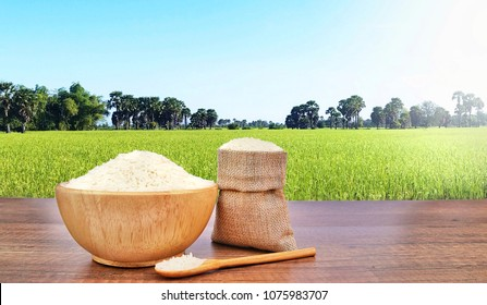 Jasmine Rice (Thai rice) in Wooden bowl and sackcloth burlap on vintage wooden desk table with the green rice field and sunlight in background.Copy space for text.