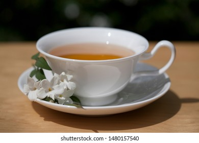 Jasmine Tea in White China Cup and Saucer Decorated with a Bunch of White Jasmine Flowers on a Table