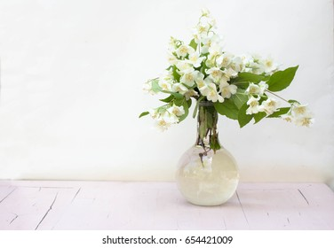 Jasmine in a vase on a table on a white background