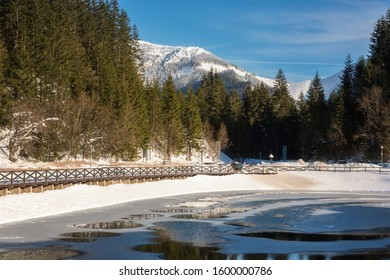 Jasna ski resort in Low Tatras, Slovakia (Slovensko). Beautiful winter landscape with artificial lake surrounded by fir tree forest, mountains and blue sky