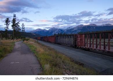 JASPER, CANADA - SEPTEMBER 5, 2016: view of the Canadian Rockies, with long line of rail cars in the foreground.