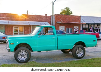 Jasper, Florida – May 17, 2019: A small town street scene with a restored classic pickup truck in front of a bar in the downtown business district.