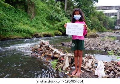Java, Indonesia - 16.01.2021: A girl protests against the pollution of the river by plastic garbage. Holding a poster that says crestfallen.