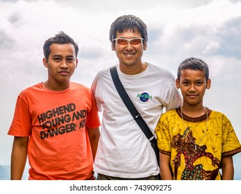 JAVA, INDONESIA - AUGUST 23, 2011: Tourist with local young boys at Candi Ceto Hindu temple, Java, Indonesia.