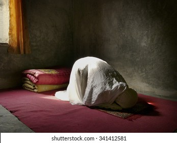 JAVA, INDONESIA - JULY 13, 2007: A disabled 45-year-old Muslim Indonesian woman suffering from facial cancer performs midday prayers on July 13, 2007 in Bandung, West Java, Indonesia.