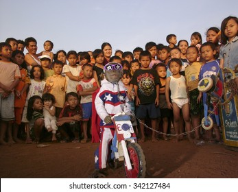 JAVA, INDONESIA - May 23, 2008: A gray macaque monkey wearing a stars-and-stripes Evel Knievel suit performs in a slum on a toy wooden motorcycle on May 23, 2008 in Jakarta, Java, Indonesia.