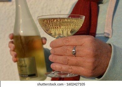 Javea, Alicante / Spain - December 31 2019:  Woman holding a crystal glass and bottle of Freixenet Cava at a party