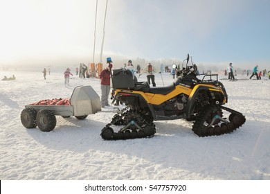 JAVORNIK, CZECH - 31 December 2016: Parked yellow snowmobile CAN-AM OUTLANDER in a winter setting, winter scooter