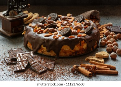 Jawor, Poland - Spring 2018: A delicious homemade cheesecake with a chocolate glaze decorated with nuts, delicacies, cookies and wafers. There are spices and sweets around.