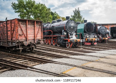 Jaworzyna Slaska, Poland - August 2018 : Man with a child looking at the old disused retro train locomotives and carriages on the side tracks in the depot in the Museum of Industry and Railway