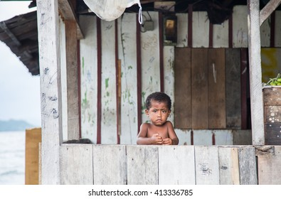 JAYAPURA, PAPUA, INDONESIA - CIRCA FEBRUARY 2016: Small Papuan boy standing at a porch with a sad face
