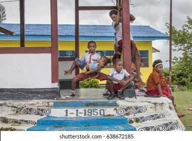 Jayapura, West Papua, Indonesia, February 17th, 2016: Schoolkids resting outside a school house