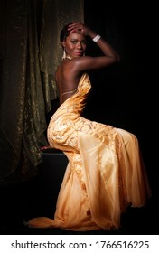 Jazz age African diva posing in backless golden dress with elaborate diamond jewelry in front of a black and gold background