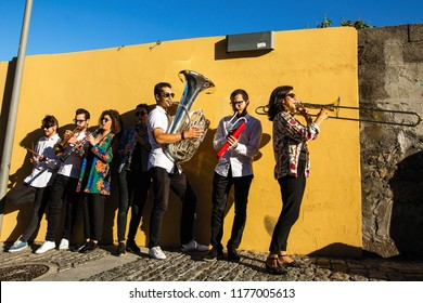 Jazz band, a group of musicians play music on the street near the yellow wall.