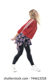Jazz dance female dancer in red tracksuit, checked shirt and leggings swinging motion. Full body length portrait isolated on white background.