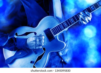 jazz guitarist playing guitar live on stage under blue light