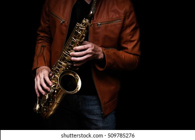 Jazz saxophone musician in the leather jacket, closeup.