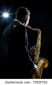 A jazz saxophone player facing the audience as he plays in a club - intentional flare
