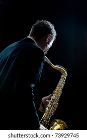 A jazz saxophone player facing the audience as he plays