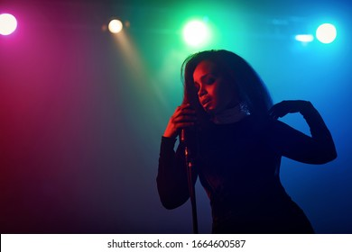 A jazz singer performs on stage. Afro.