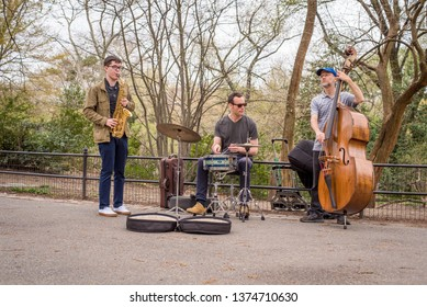 Jazz trio, alto saxophone, drums, and standup bass, play and busk in New York City's Central Park amongst the trees on the asphalt path