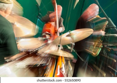 Jazz trio performing on stage, intentional dynamic motion blur with lens, long exposure