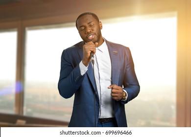 Jazzman singing on sunlight background. Beautiful perfomance of black arist. Talanted afro american jazz singer.