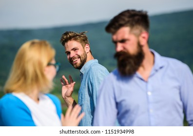 Jealous concept. Man with beard jealous aggressive because girlfriend interested in handsome passerby. Passerby smiling to lady. Husband strictly watching his wife looking at another guy while walk.