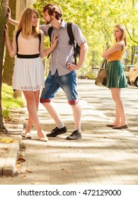 Jealous girl looking at flirting couple outdoor. Happy young woman and man couple dating. Summer romance affair.