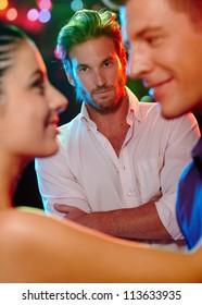 Jealous man looking at dancing couple, flirting girlfriend in nightclub.